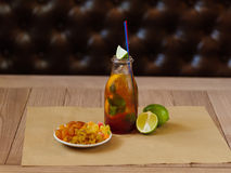A plate with raisins, dried apricots, a cocktail with lemon, lime and mint on a blurred wooden background. Stock Photos