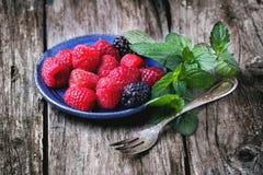 Plate of raspberries and blackberries Stock Photos