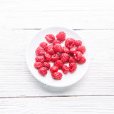 Plate with raspberries on white wooden table. Royalty Free Stock Photo