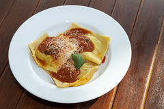 Plate with ravioli grandi on wooden table Stock Photo
