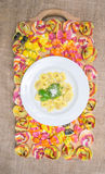 A plate of ravioli pasta with pesto sauce on a wooden board full of ravioli on a canvas Royalty Free Stock Image