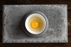 Plate with raw broken egg, shell on concrete slab stock photography