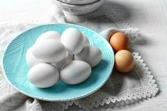 Plate with raw eggs. On kitchen table Royalty Free Stock Photography