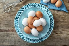 Plate with raw eggs. On wooden background Royalty Free Stock Photography