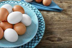 Plate with raw eggs. On wooden background Royalty Free Stock Images