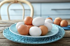 Plate with raw eggs. On wooden table Stock Photos