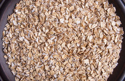 Plate with raw oatmeal background Royalty Free Stock Images