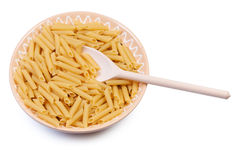 Plate with raw pasta and wooden spoon. Royalty Free Stock Image