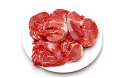 A plate of raw stewing steak. Plate of raw stewing steak on a white background stock images