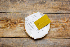 Plate and receipt bill for payment by credit card wooden table background top view. Plate and receipt bill for payment by credit card on wooden table background Royalty Free Stock Photo