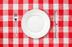 Plate on red checked tablecloth Royalty Free Stock Photos
