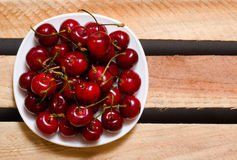 Plate with red cherries on wooden plates, top view, space for text Stock Photography