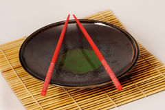 Plate with red chopsticks. Bamboo place mat with Asian dinner plate and red chopsticks Royalty Free Stock Photo