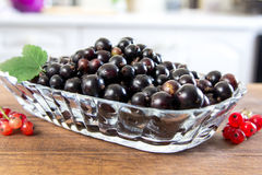 Plate of red currant on the wooden board. Top wiew, closeup. White kitchen at the background. A plate of red currant on the wooden board Stock Image