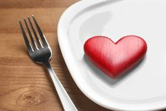 Plate with red heart and fork on wooden table. Healthy diet concept. Plate with red heart and fork on wooden table, closeup. Healthy diet concept stock photo