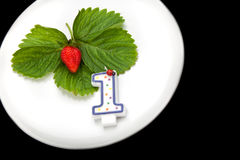 A plate with red strawberry and candle Royalty Free Stock Photography