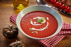 Plate of red tomato cream soup. In rustic kitchen, served on checked napkin with greens and white sauce. Fresh and healthy organic food concept stock photos
