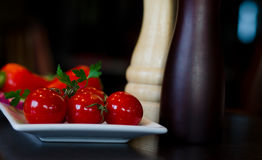 Plate of Red Tomatoes with Salt and Pepper Mills Stock Photo