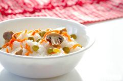 Plate with the rice. And the vegetables on the kitchen table Royalty Free Stock Photography