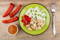 Plate with rice, fried chicken meat and sweet pepper, sauce. Fork on wooden table. Top view Stock Images