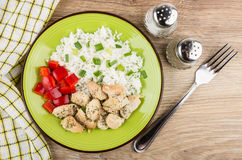 Plate with rice, fried chicken meat and sweet pepper, spices. Fork on wooden table. Top view Royalty Free Stock Image