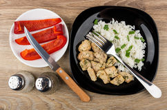 Plate with rice, fried chicken meat, sweet pepper, spices, knife. And fork on wooden table. Top view Royalty Free Stock Images
