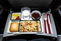 Close up of a plate of food served on the airplane. Plate of rice salad, bread, fruits, tea, and water served on an airplane stock photo