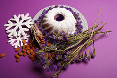 A plate with a ring cake, lit candle, cinnamon, almond and snowflakes on a bright violet background, top view. A ring cake sprinkled with powdered sugar, a Royalty Free Stock Images