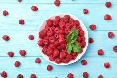 Plate with ripe raspberries on wooden table, top view. Plate with ripe aromatic raspberries on wooden table, top view Royalty Free Stock Images