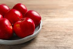 Plate with ripe red apples. On wooden background stock images