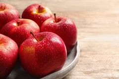Plate with ripe red apples. On wooden background royalty free stock photography