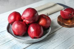 Plate with ripe red apples. On white wooden table Royalty Free Stock Photos