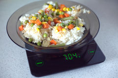 Plate with rise and vegetables on kitchen scales closeup Stock Photo