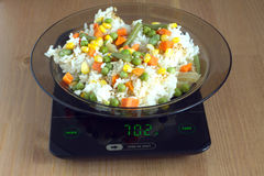 Plate with rise and vegetables on kitchen scales closeup Stock Images