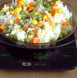 Plate with rise and vegetables on kitchen scales closeup Royalty Free Stock Photos