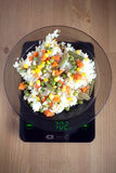 Plate with rise and vegetables on kitchen scales closeup Stock Image