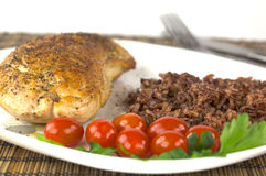 Plate with roast turkey with brown and red rice and whole cherry Stock Photos
