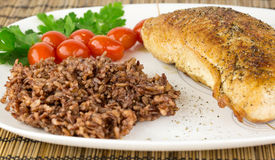 Plate with roast turkey with brown and red rice and whole cherry Royalty Free Stock Images