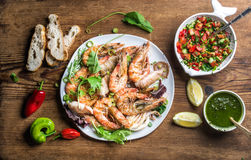 Plate of roasted seafood with fresh leek, green salad, peppers, lemon, bread, pesto sauce over wooden background, top. Plate of tiger prawns and pieces of Royalty Free Stock Photo