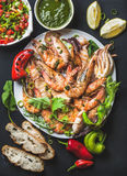 Plate of roasted tiger prawns and octopus pieces with fresh leek, salad, peppers, lemon, bread, pesto sauce over black Stock Photos