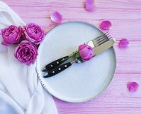 Plate, rose flower fork, knife romantic dinner on a pink wooden background stock images