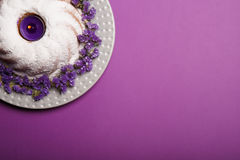 A plate with round cake sprinkled with powdered sugar and a candle in the center on a bright violet background. Royalty Free Stock Photography