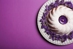 A plate with round cake sprinkled with powdered sugar and a candle in the center on a bright violet background, top view Stock Photo