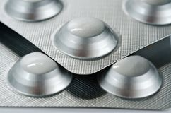 Plate with round medical pills silver color close-up shot.  royalty free stock photography