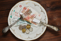 Plate with russian rubles money. Different rubles notes and coins on the plate with golden ornamentation and vintage silver fork and knife stock images