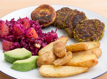 Plate of salad, falafel, avocado and baked potatoes. Red cabbage salad, oranges, falafel, avocado and baked potatoes on white plate on beige wood table Stock Photography