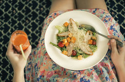 A plate with a salad on female knees and glass of carrot juice. View from above. The concept of food and healthy lifestyles. Stock Images