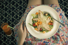 A plate with a salad on female knees and glass of carrot juice. View from above. The concept of food and healthy lifestyles. Royalty Free Stock Photography