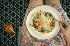 A plate with a salad on female knees and glass of carrot juice. View from above. The concept of food and healthy lifestyles. Stock Photos
