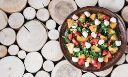 A plate of salad with mozzarella and vegetables on a wooden background. stock photography